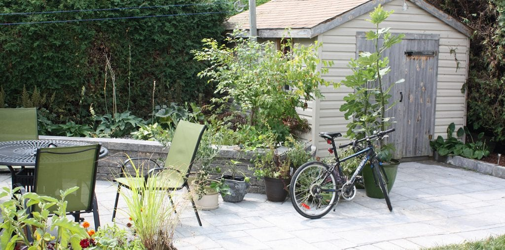 Backyard with retaining wall, shed and bicycle